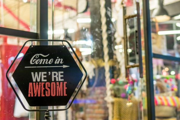 "Storefront window with a sign that says ""Come in. We're awesome."""