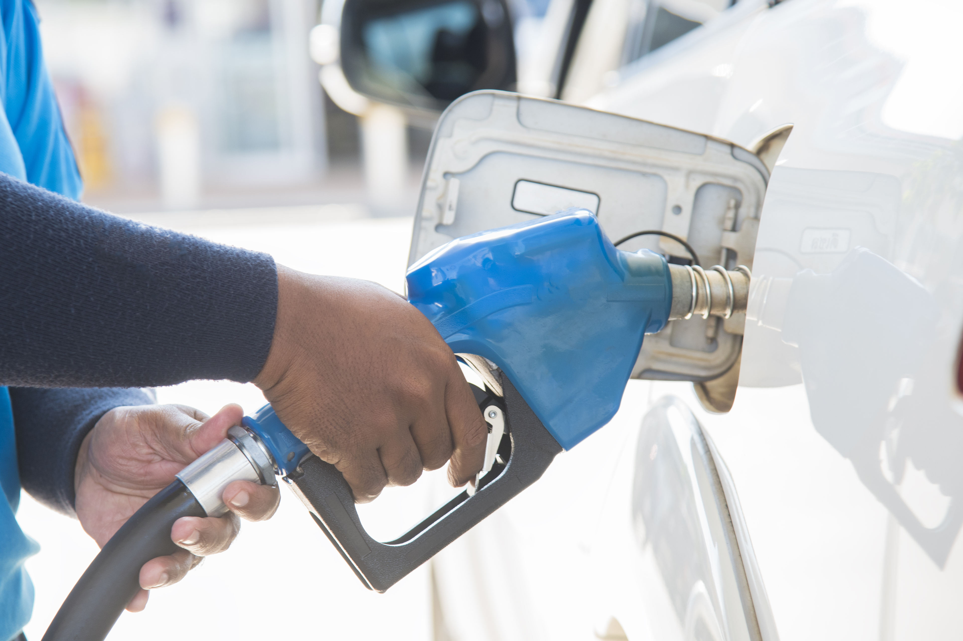 Person filling up car with fuel at a gas station.