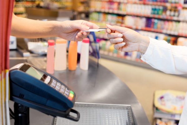 Convenience store operator exchanging a credit card with a consumer