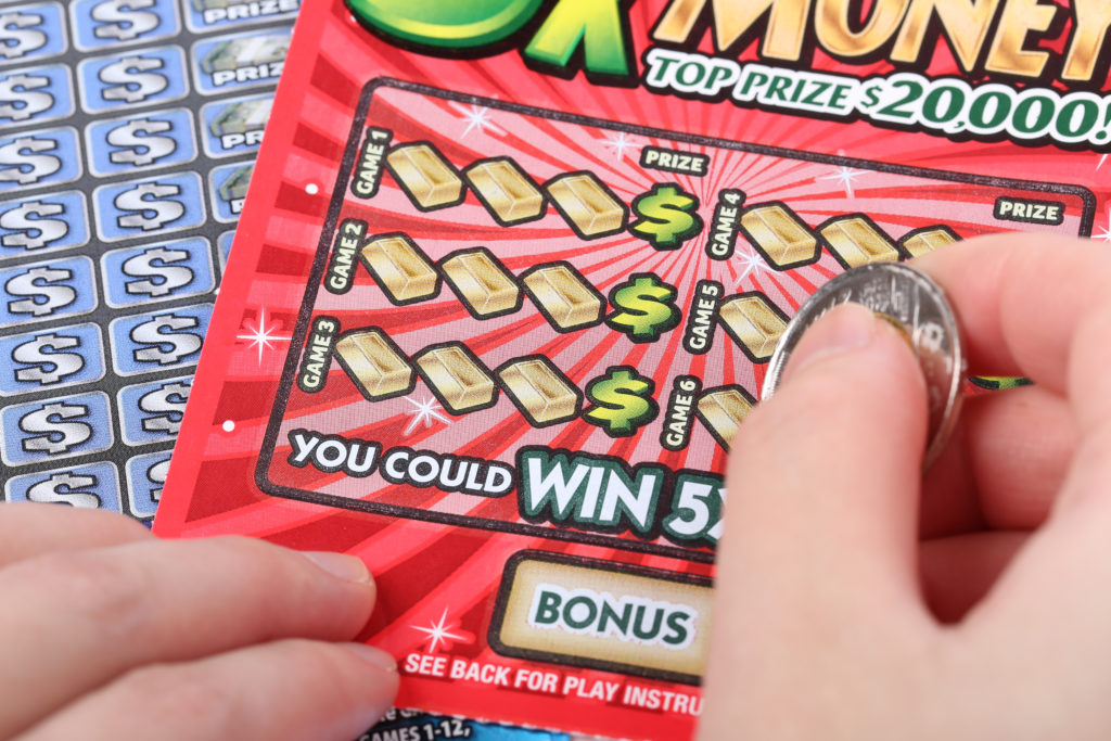 Person scratching off a lottery ticket.